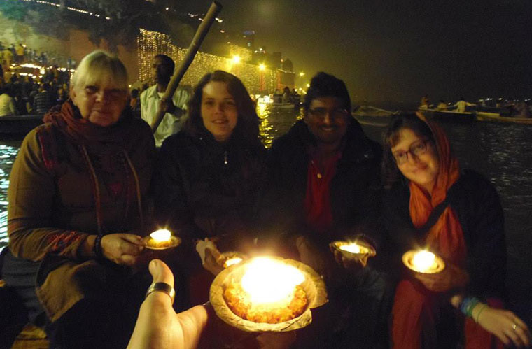 tourists floating diyas in ganga